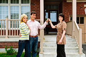 Couple being handed the keys to their home.